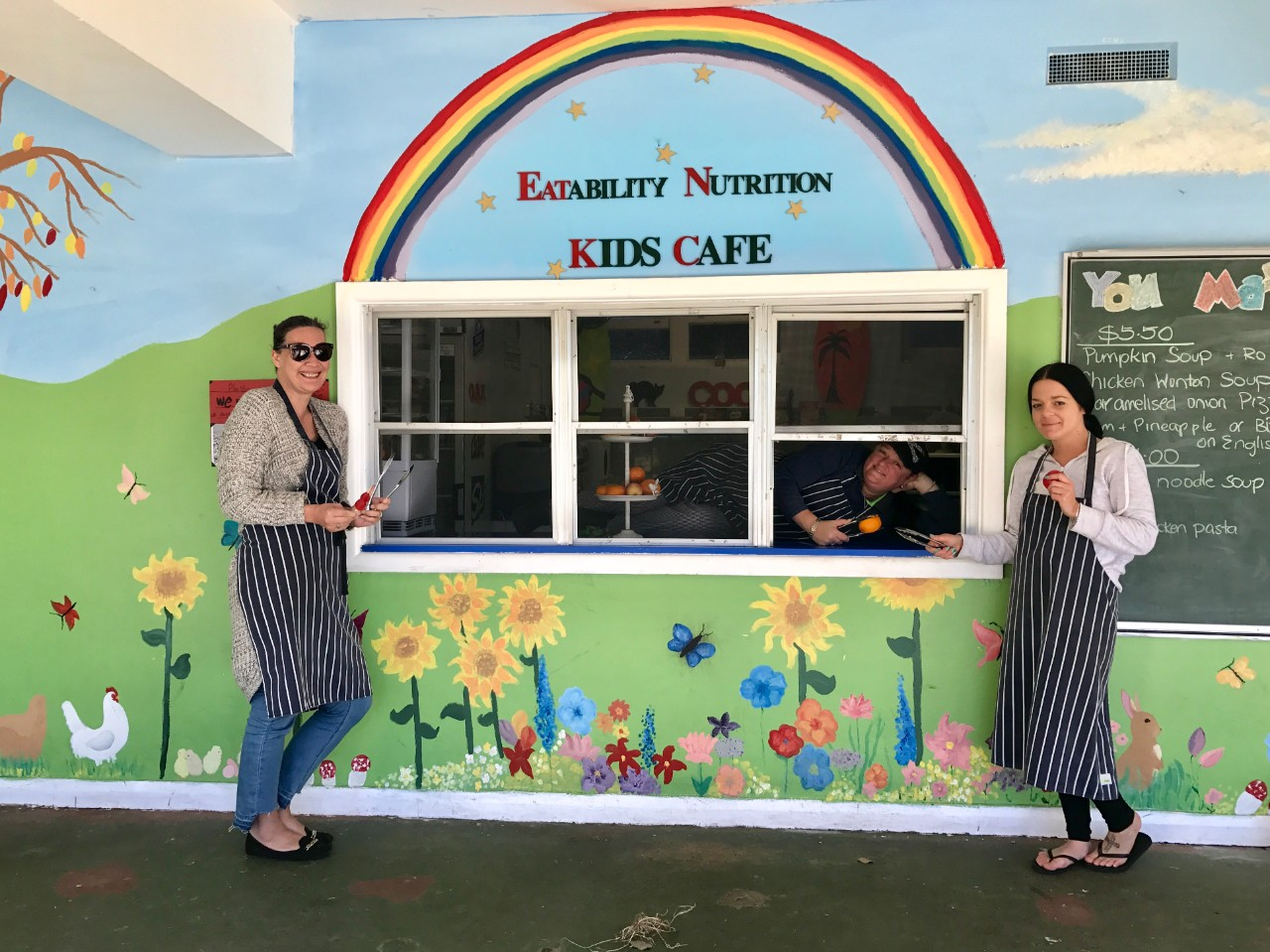 1 woman inside and 2 women standing outside the bright and colourful canteen.
