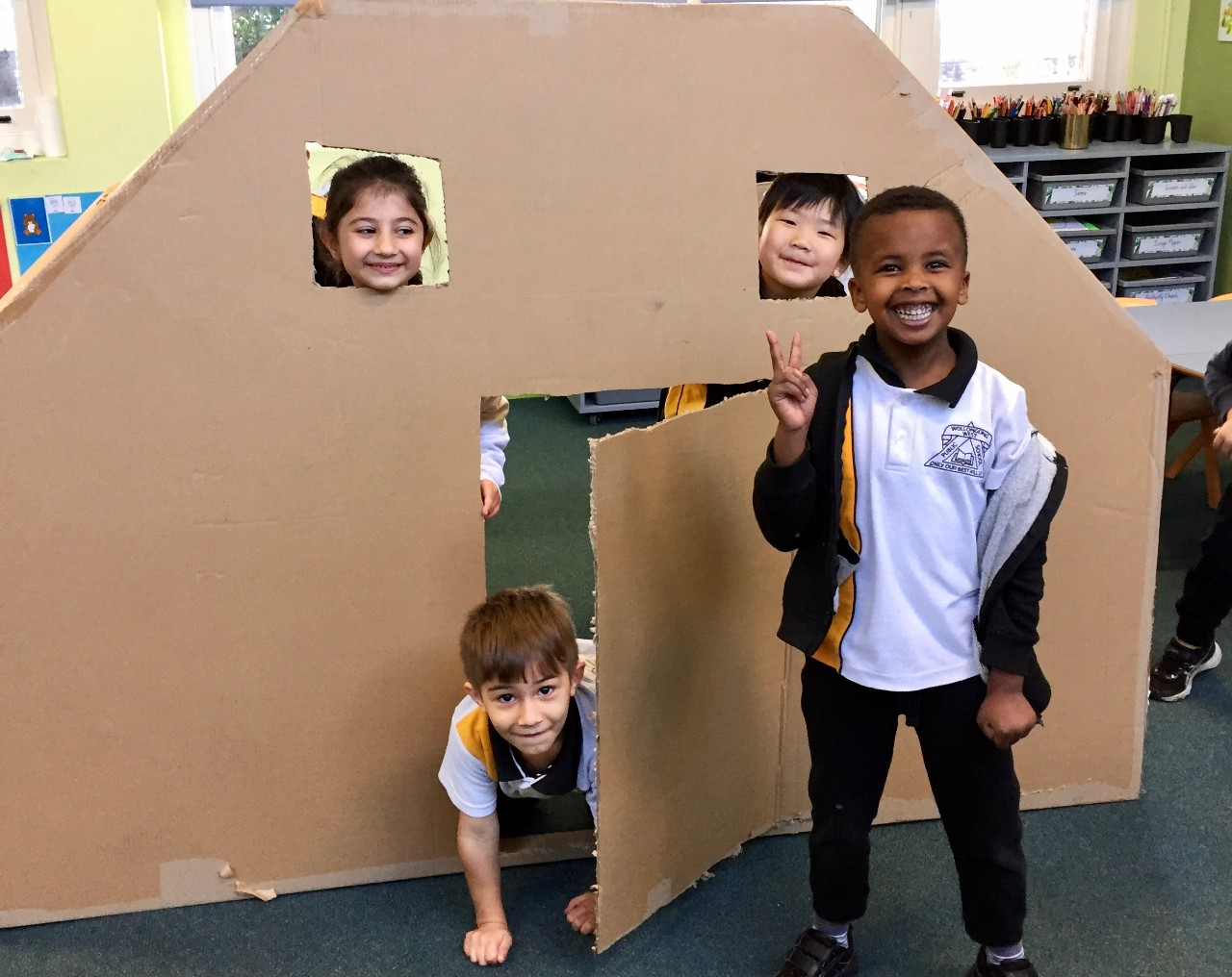 Four children smiling and playing in a house made from cardboard.